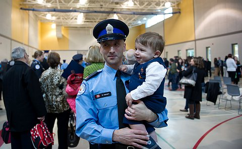 A officer in uniform with his baby son in his arms.