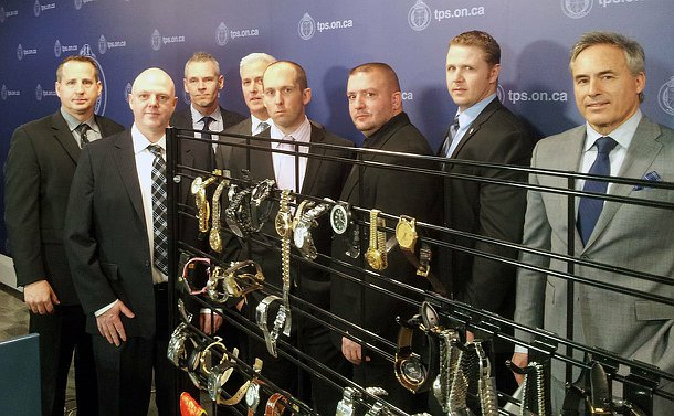 A group of men standing in-front of a display of stolen wrist watches.