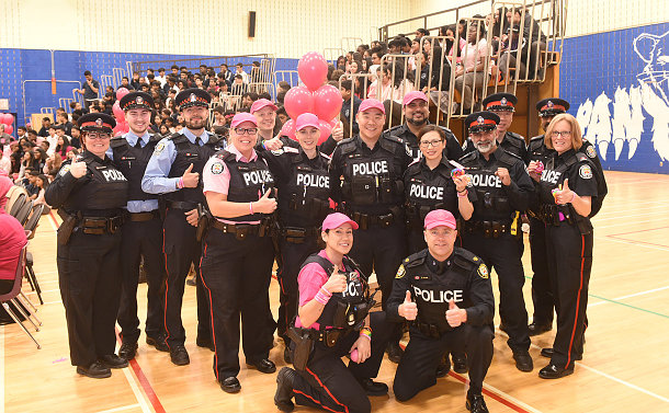 A group of police officers in pink shirts and hats