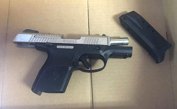 A silver handgun with a clip in a box