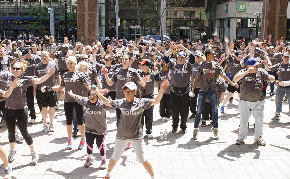 A group of men and women in matching Torch Run T-shirts with arms raised over their heads