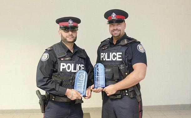 Two men in TPS uniform holding awards