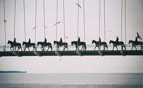 A line of officers on horses in silhouette crossing a foot bridge