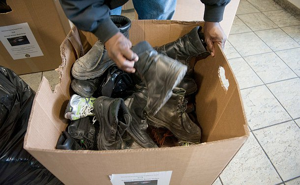 A pair of hands holding boots above a box full of boots