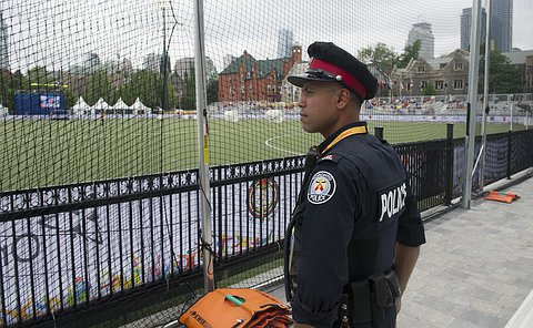 An officer standing on the side of a Field hockey field watching the game.