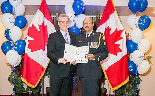 Two men, one in TPS uniform, holding a certificate in front of Canadian flags
