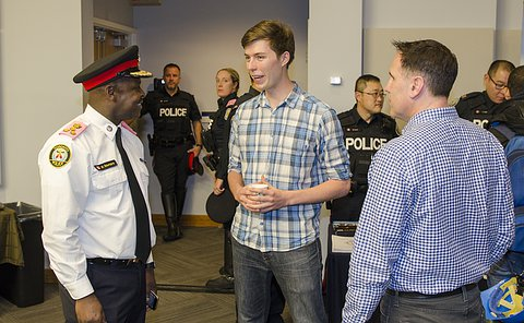 A man in TPS uniform speaks to another man