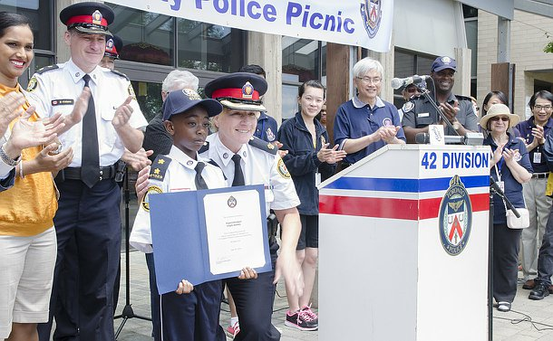 A woman in TPS uniform poses with a boy in TPS uniform holding a certificate as other people clap