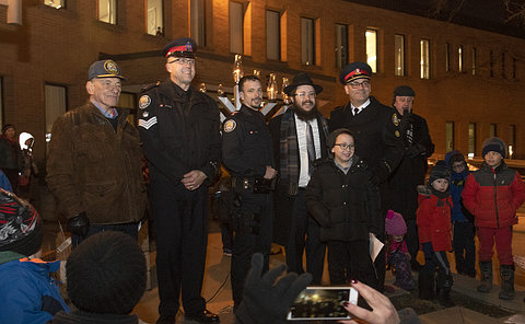 A group of people, some in TPS uniform, beside a menorah