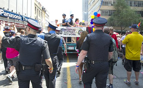 A group of people in TPS uniform walking behind a float with a banner where two men in TPS court uniform stand on the float
