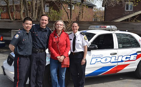 Two men and one woman in TPS uniform with another woman standing in front of a TPS scout car