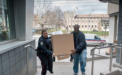 A woman in TPS uniform and a man carry a large box up an outdoor staircase with a police van in the background