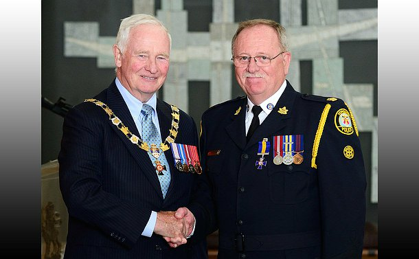 Two men stand together, one wearing the chains, one in TPS uniform