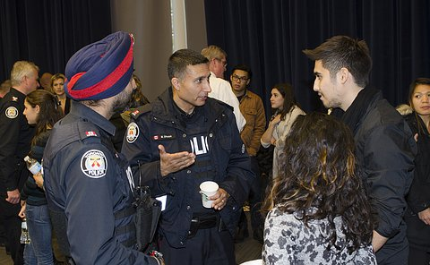 Two men in TPS uniform talk to a man and a woman