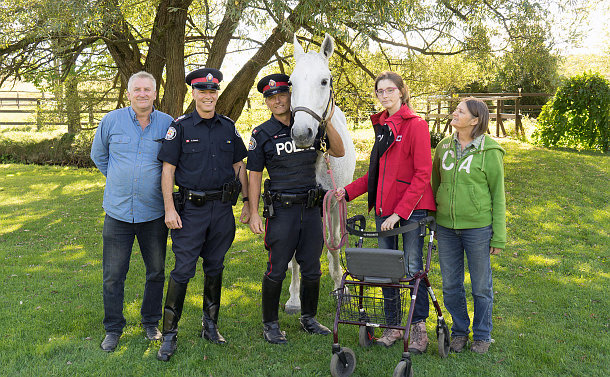 Man and two women with two men in police uniforms stand next to a white horse