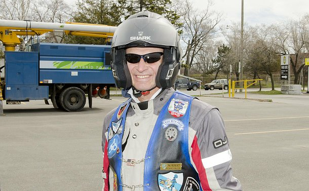 Close-up of a man smiling and wearing a motorcycle helmet, jacket and sunglasses