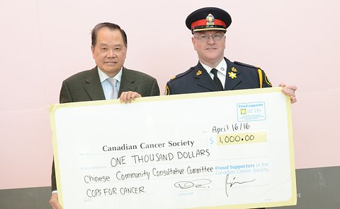 Two man, one in a police uniform hold a large cardboard cheque in the amount of 1,000 dollars
