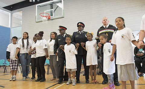 A group of men and women in TPS uniform hold hands with children