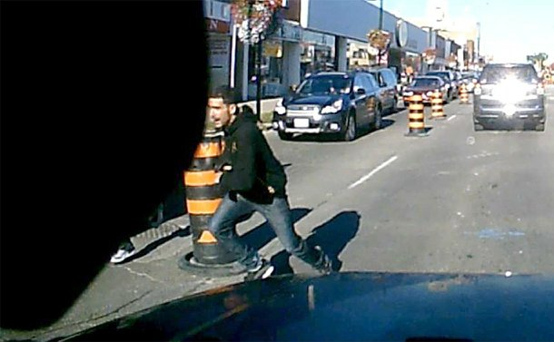 A man running in the curb lane of a road. View is from inside the car