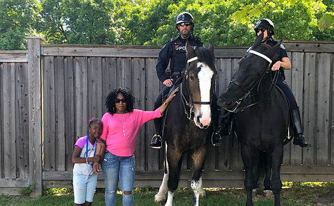 A woman and girl with two TPS officers on horseback