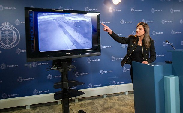 A woman at a podium points at a TV screen with security video footage of a driveway