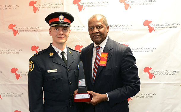 A man in TPS uniform stands beside another man holding an award