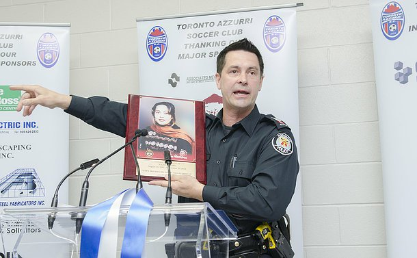 A man in TPS uniform at a podium holds a plaque