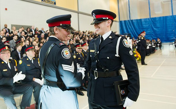 a woman in uniform shaking hands with another woman in uniform