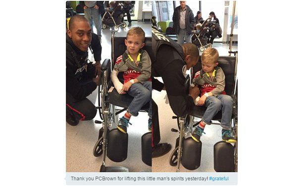 A man in TPS uniform beside a boy in a wheelchair