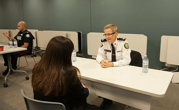 A woman in TPS uniform sits across the table from another woman