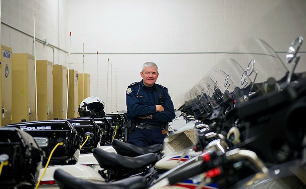 An officer sitting on a motorcycle with a few bikes behind him and in front of him, all lined up.