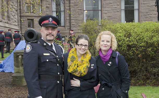Close up of a man in a police uniform and two women standing in front of a building
