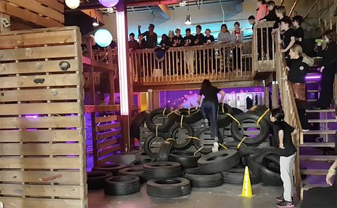 A group of kids on an obstacle course made up of car tires on ropes
