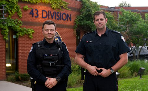 Two officers in uniform standing in front of 43 division