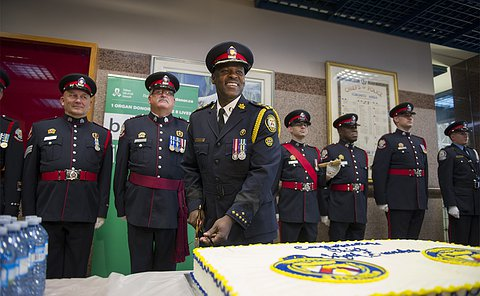 A man in TPS uniform cuts a cake with other men in TPS uniform behind him