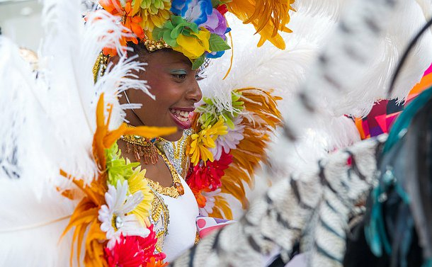 A girl in an colourful costume looking sideways and smiling.
