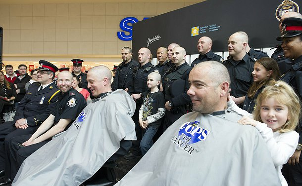 A large group on a stage including men and women in TPS uniform, many with their heads shaved