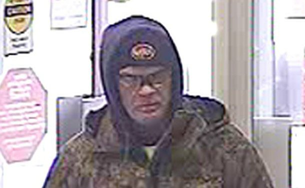 A man in a hood and sunglasses in a security camera image