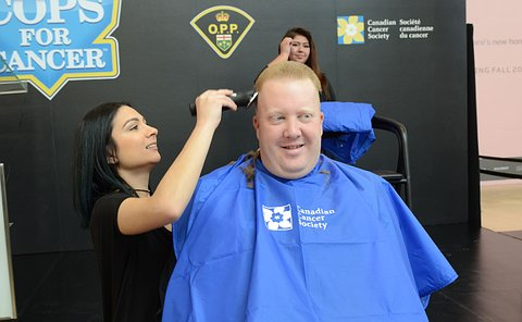 Man sitting in a chair, while a woman is shaving his head with an electric shaver