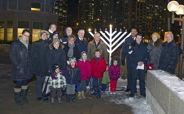A Group of police officers and members of the Jewish community in front of the menorah at 32 Division