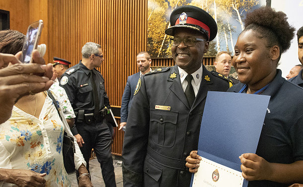 A man in TPS uniform with a girl holding a certificate