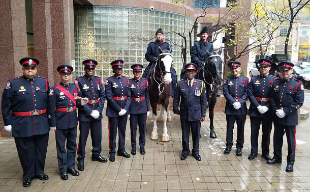 A group of men and women in uniform with two horses
