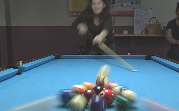 A woman breaks on a pool table