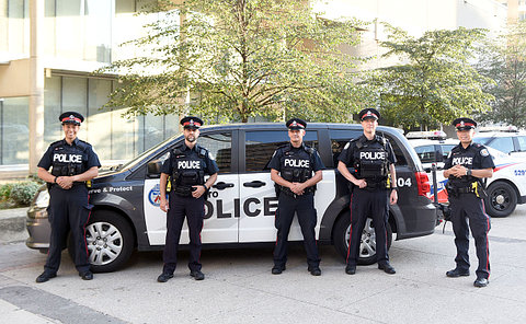 Group of men and women, wearing police uniforms, standing in a parking lot in-front of various police vehicles.