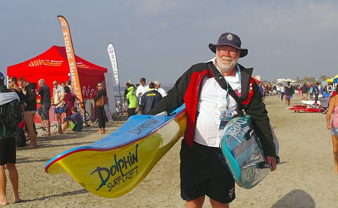 A man carries a kayak under one arm in a beach setting