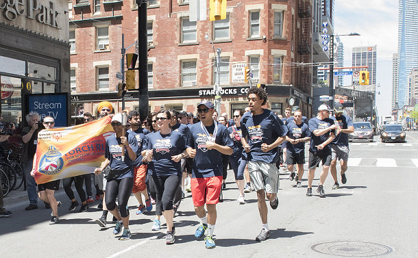 A group of people running, one person carries a torch