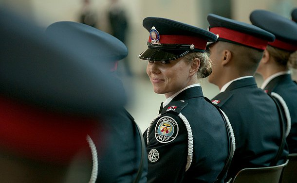 A woman in TPS uniform smiles at the camera while seated amongst others in TPS uniforms.