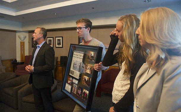 A man speaks beside a teenage boy holding a framed newspaper and photos alongside a teenage girl and a woman
