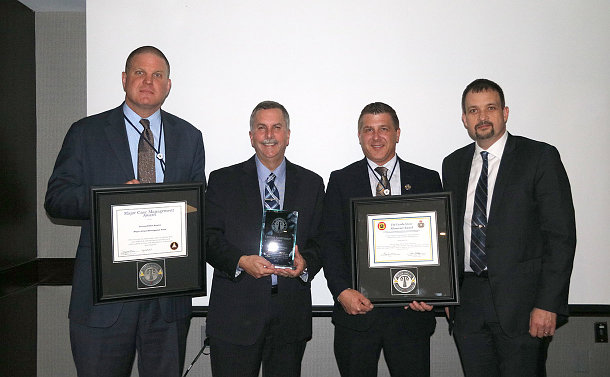Four men standing with plaques and certificates