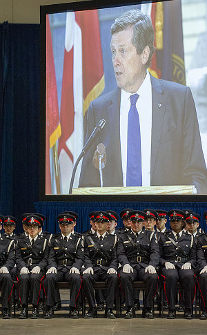 A group of TPS officers seated with a man on a large screen